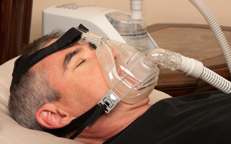 Schlafender Mann mit Atemmaske bei einer Schlafapnoe
